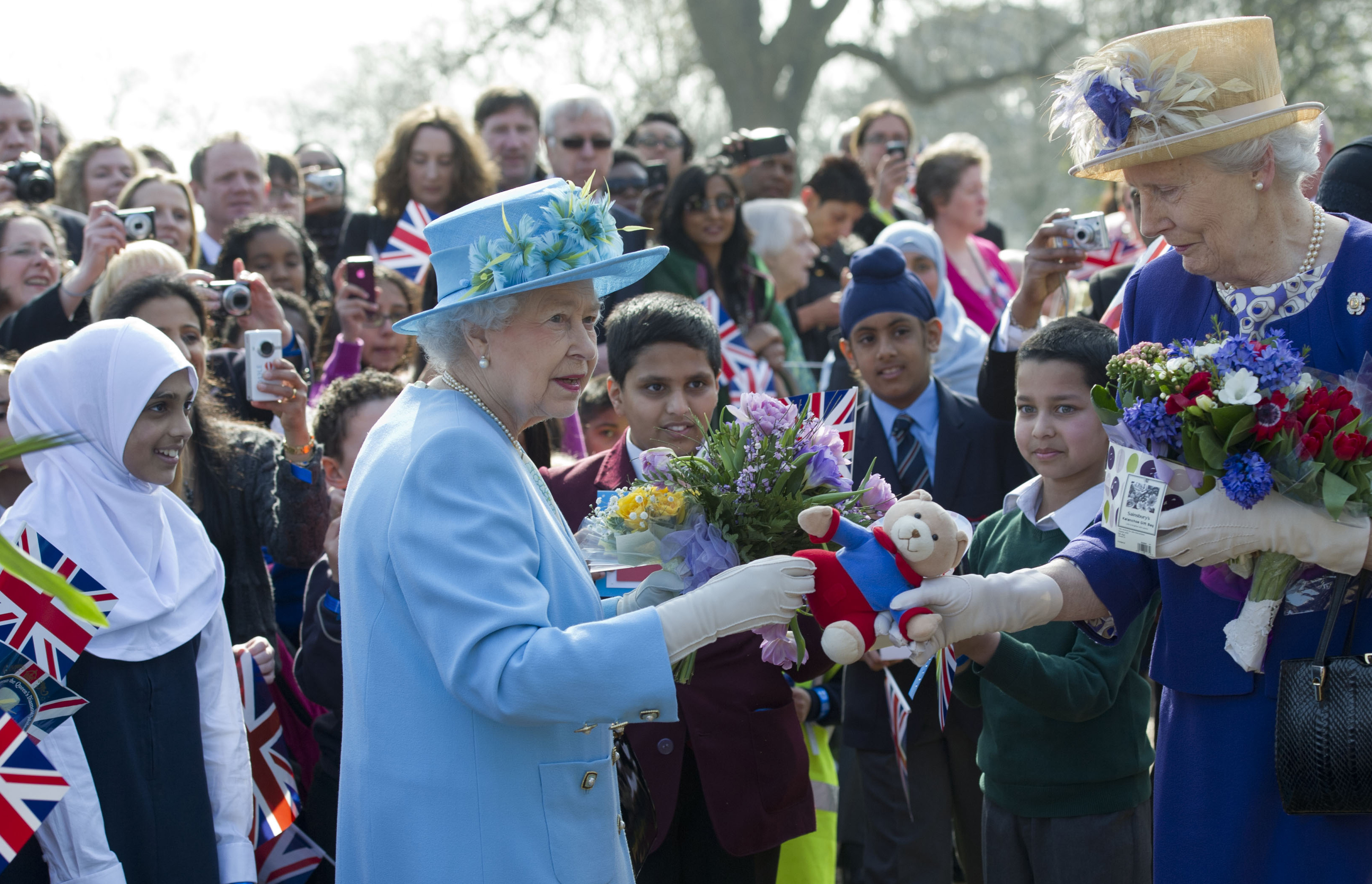 Britain's Queen Elizabeth II (L) hands gifts she was presented with to a lady-in-waiting