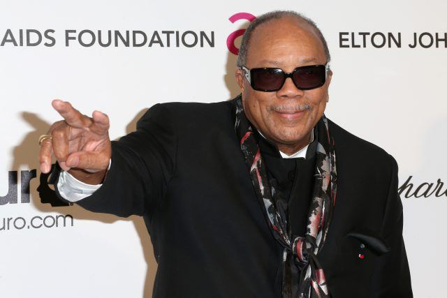 Quincy Jones gesturing and posing on a red carpet.