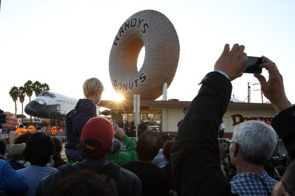 A crowd gathers outside of Randy's Donuts to watch the space shuttle Endeavour