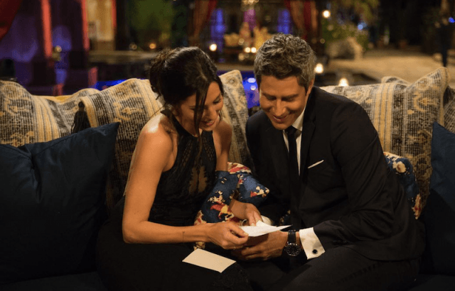 Rebecca looking at a note while sitting on a couch with Arie.