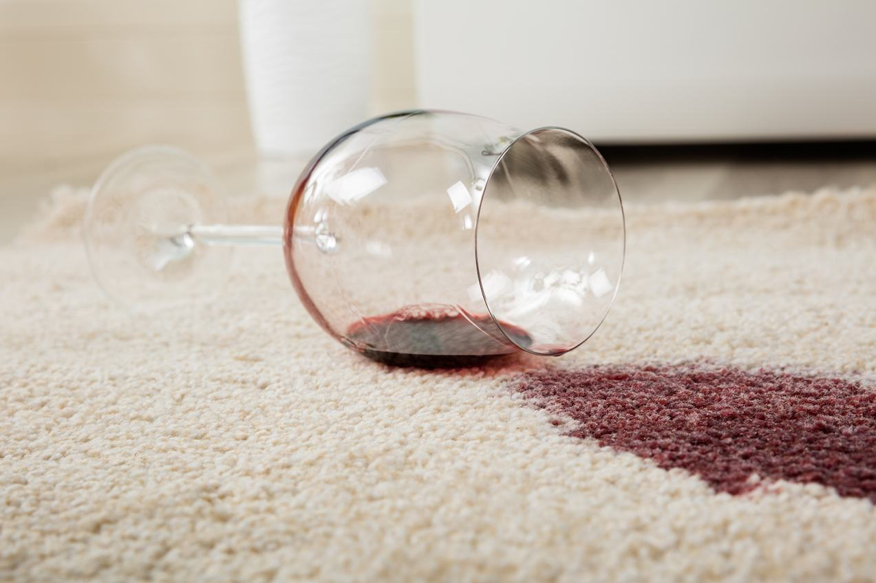 High Angle View Of Red Wine Spilled From Glass On Carpet