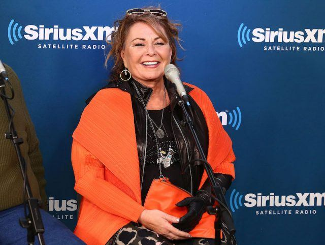 Roseanne Barr sitting in front of a microphone during a radio interview.