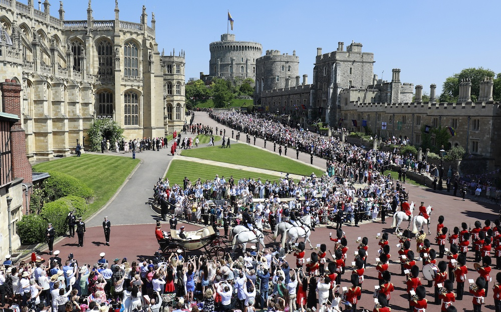 Prince Harry, Duke of Sussex and The Duchess of Sussex leave Windsor Castle in the Ascot Landau carriage during a procession after getting married at St Georges Chapel on May 19, 2018 in Windsor, England.