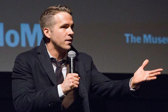 Ryan Reynolds speaking into a microphone.