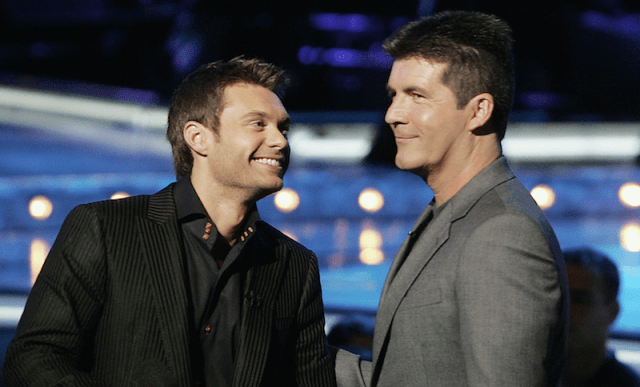 Ryan Seacrest and Simon Cowell smiling and talking together.