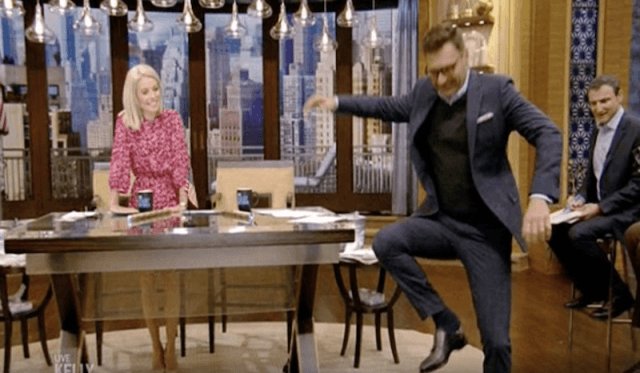 Kelly Ripa looking over at Ryan Seacrest as he fidgets with his shoe.