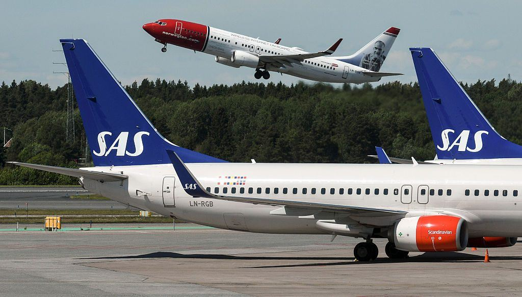 A Norwegian Boeing 737-800 takes off behind the tails of two of Scandinavian airline
