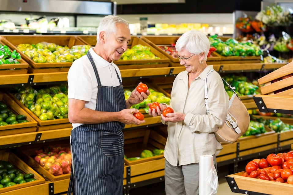 Senior customer and worker discussing vegetables in supermarket