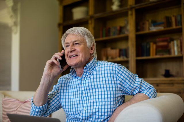 Senior man talking on mobile phone in living room at home