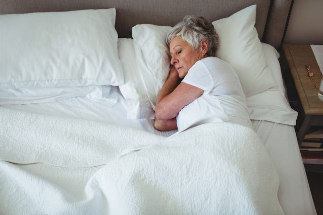 Senior woman sleeping on bed in bedroom at home