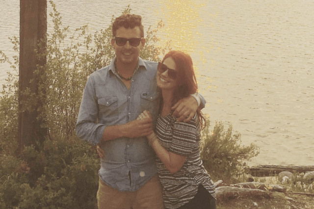 Stacie and Evan Felker posing together in front of a river.