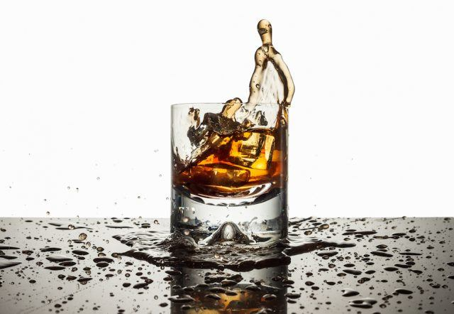 Ice cubes falling dark liquor filled glass and splashing onto counter top