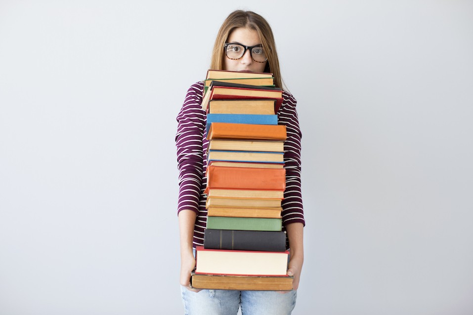 Student woman holding pile books