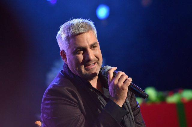Taylor Hicks singing into a microphone on stage.