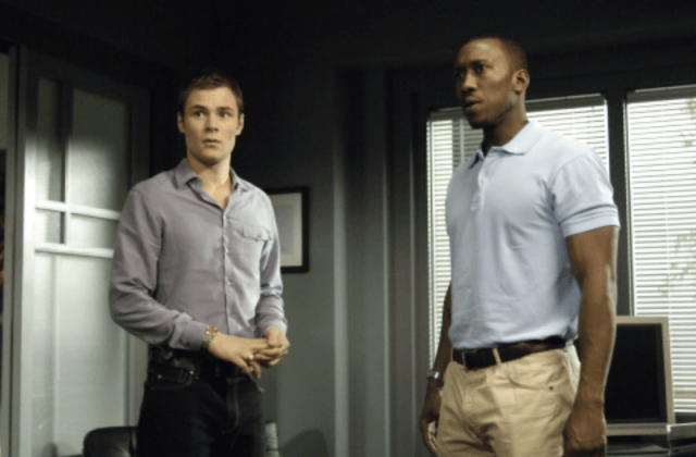 Two men speaking to each other inside a room.