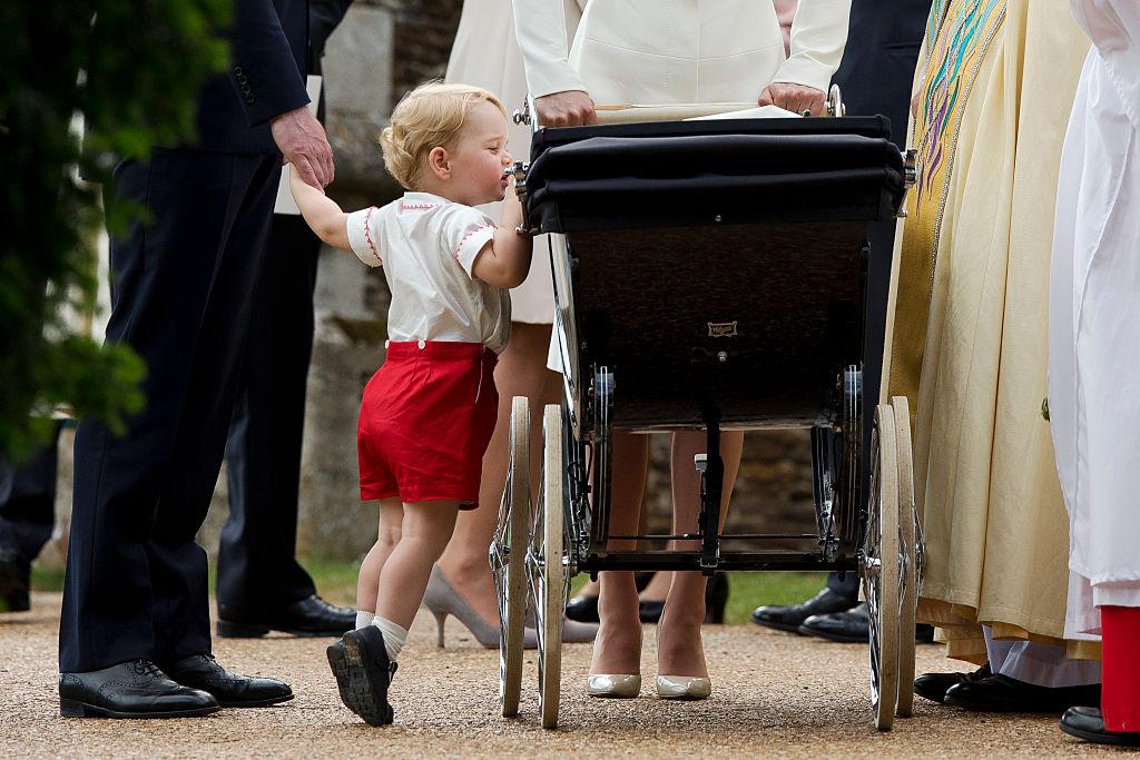 Catherine, Duchess of Cambridge and Prince William, Duke of Cambridge stand as Prince George of Cambridge looks into Princess Charlotte of Cambridge's pram