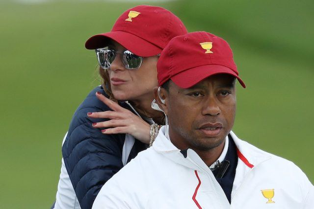Erica Herman standing behind Tiger Woods.