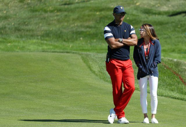 Tiger woods standing with his arms crossed next to Erica Herman.
