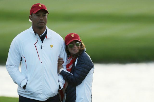 Erica Herman holds Tiger Wood's arm.