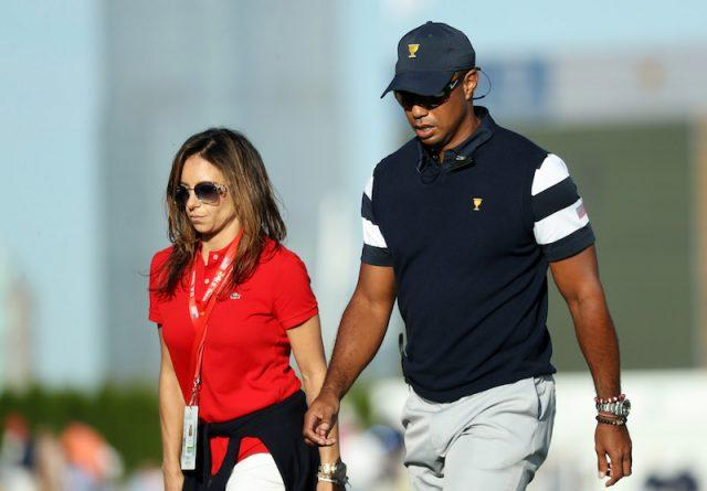 Erica Herman walking alongside Tiger Woods.
