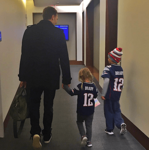 Tom Brady walking down a hallway with his children.