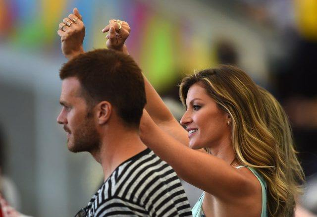 Gisele Bündchen cheers as she stands next time to Tom Brady.