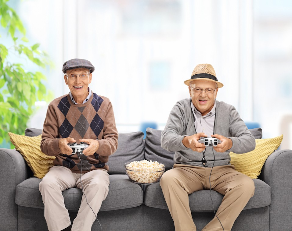 Two joyful seniors playing video games