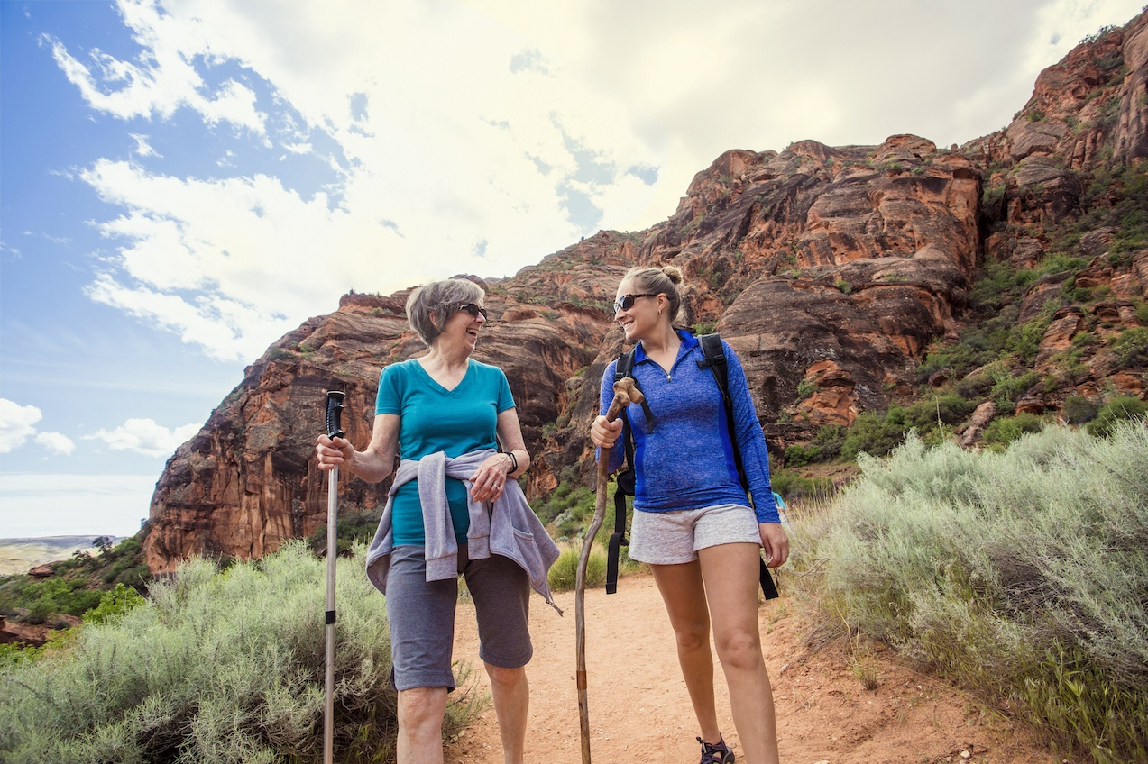 Women hiking together in a beautiful red rock canyon