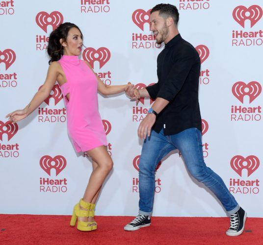 Val Chmerkovskiy and Janel Parrish posing on a red carpet.