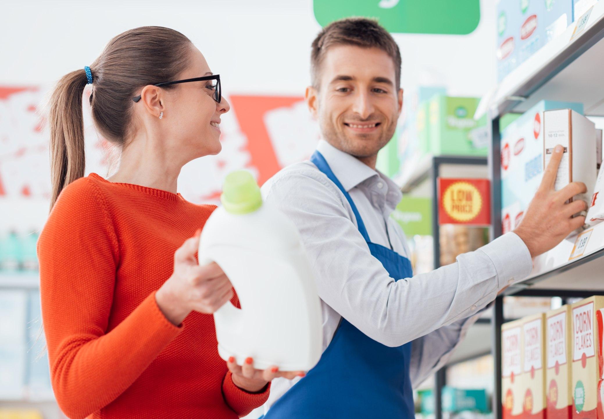 Supermarket clerk helping a customer