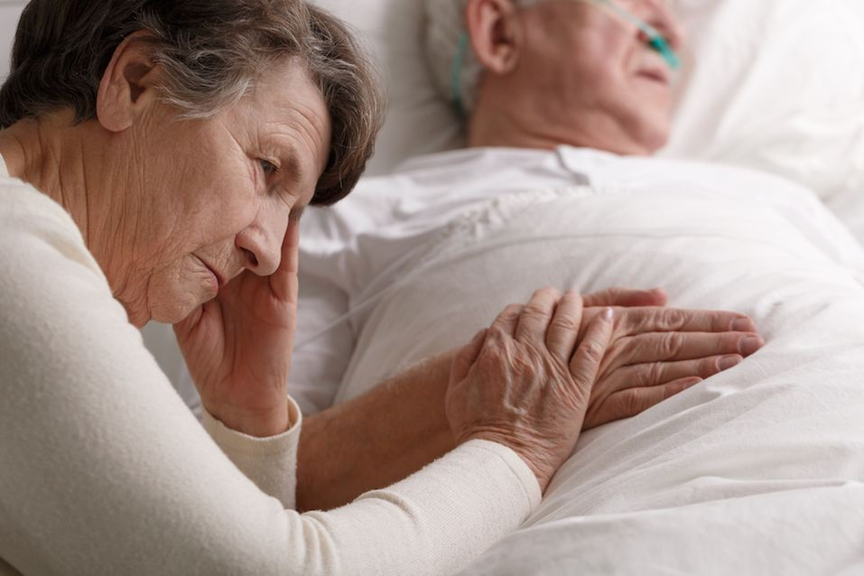 Woman holding dying husband's hand