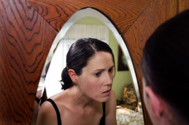 A woman looking into a mirror.