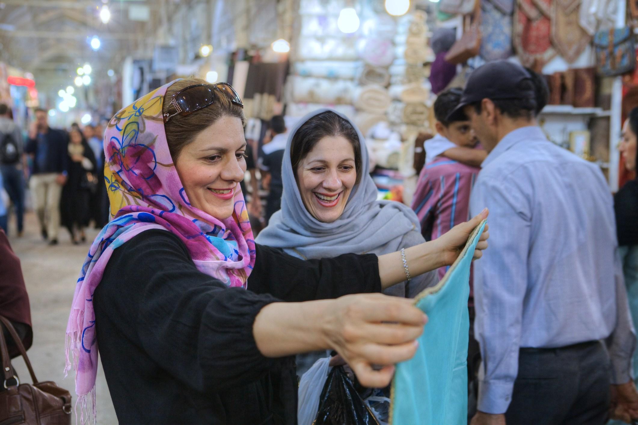 Women in hijab choose fabric in city market, Shiraz, Iran.