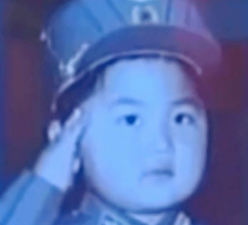 A young Kim Jong Un saluting in a photo.