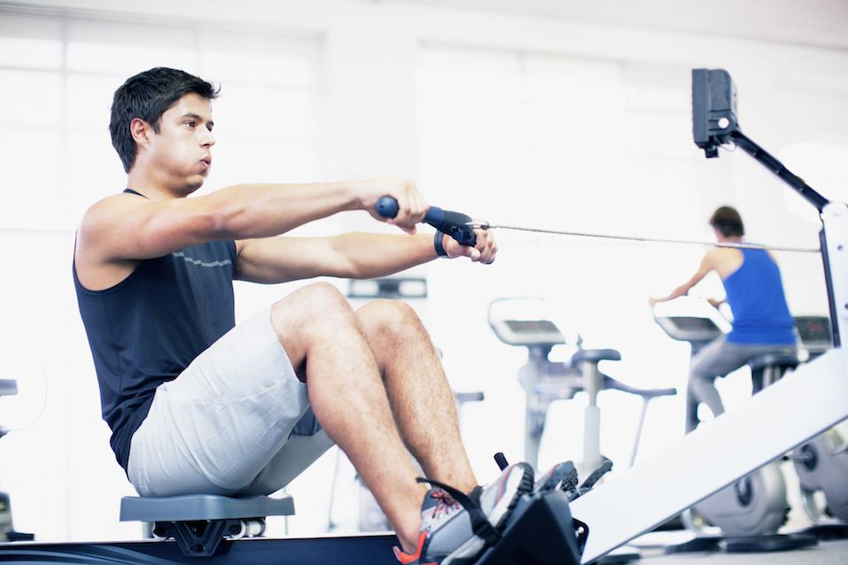 Young man exercising on a rowing machine in a gym