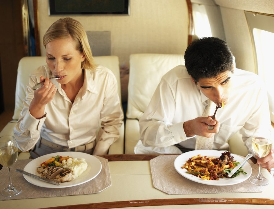 customers eating and drinking while on an airplane