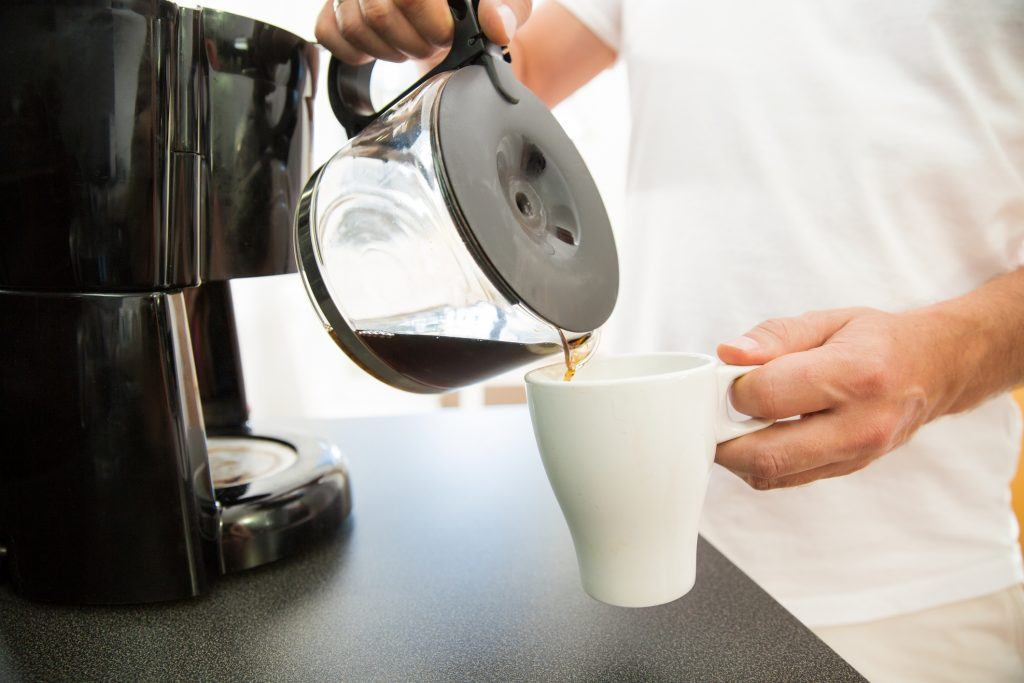 A person pours some coffee.