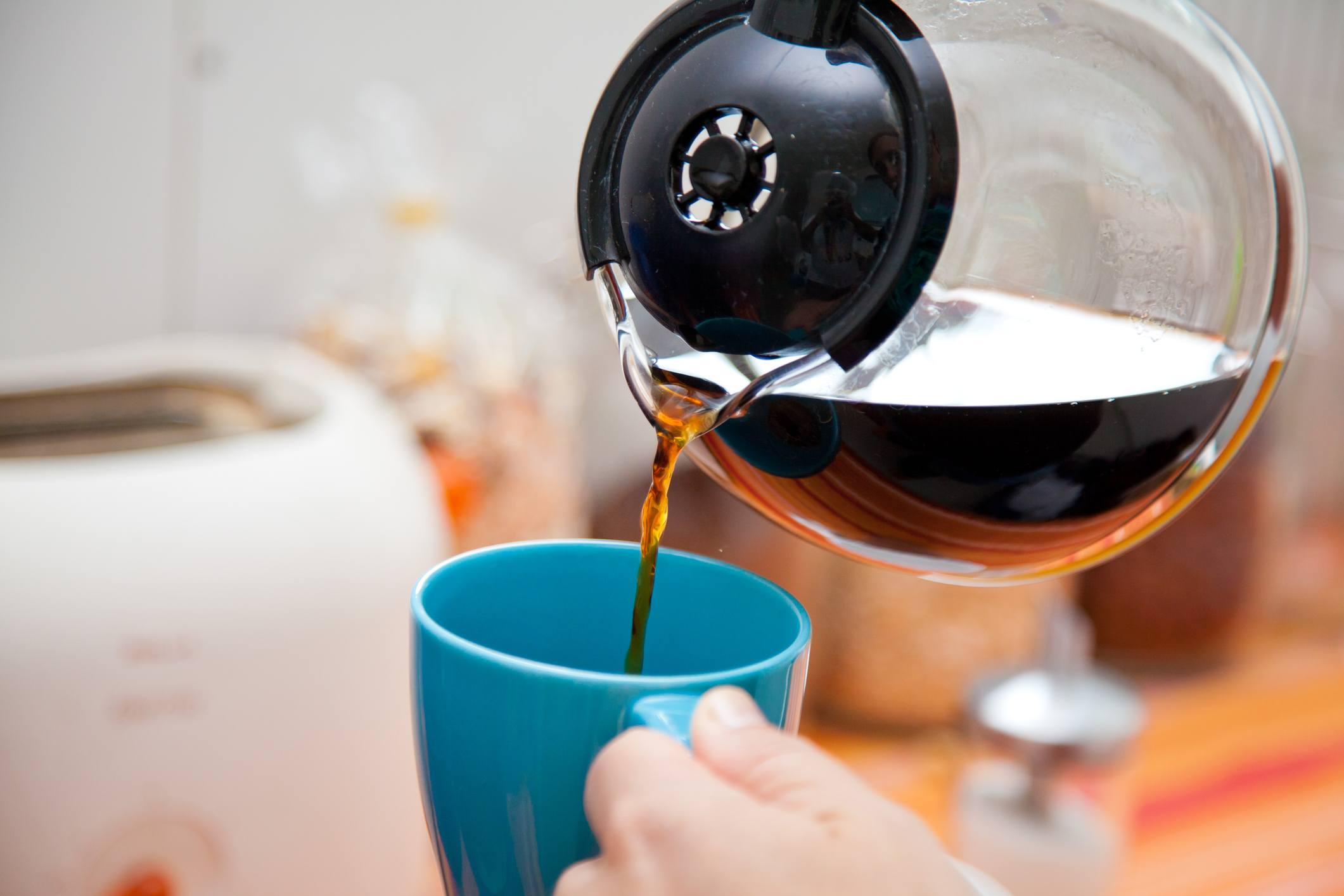 A person pours coffee from the pot.