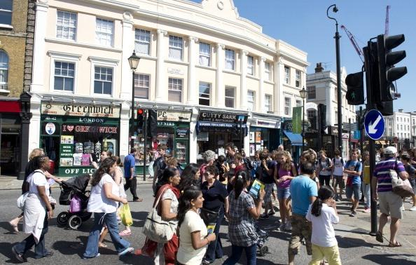 A crowd of pedestrians crosses a street