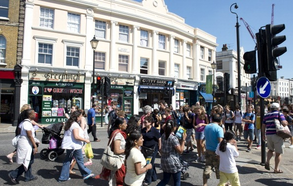 A crowd of pedestrians crosses a street in downtown Greenwich, London, on July 23, 2012, four days ahead of the London 2012 Olympic Games. Greenwich is hosting all of the equestrian events of the summer Olympics.