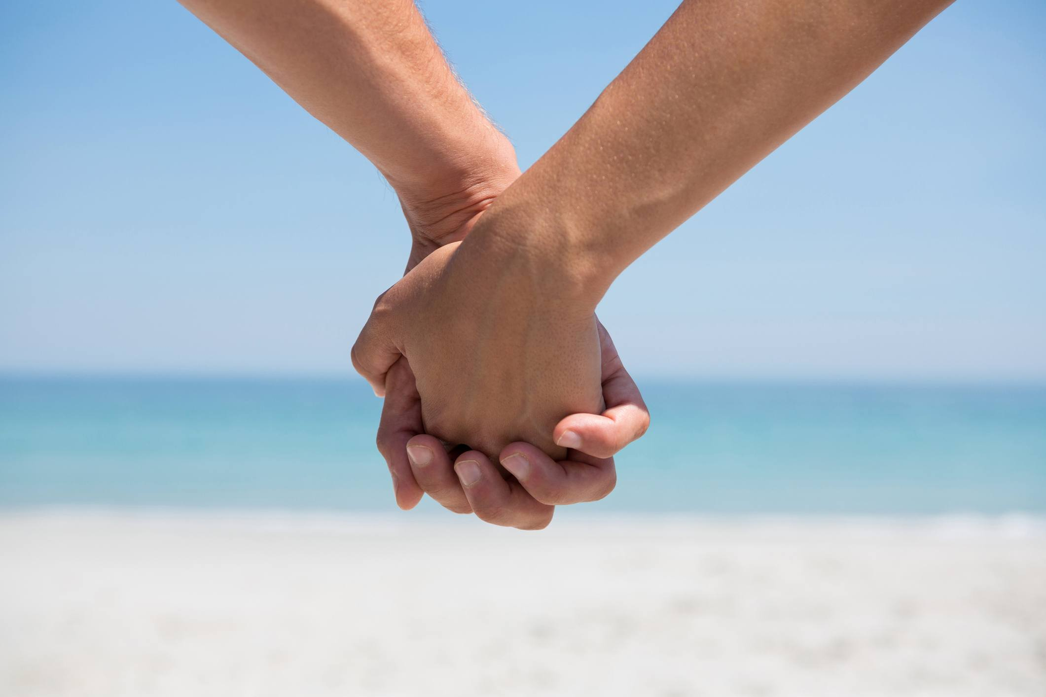 A couple holds hands at the beach.