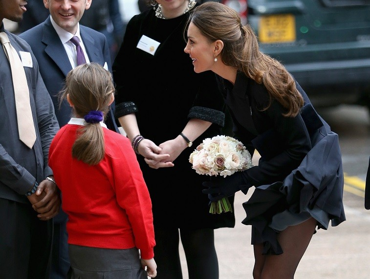 A young girl curtsies as Catherine, Duchess of Cambridge arrives at Clifford Chance to attend the Place2Be Forum at Canary Wharf on November 20, 2013 in London, England.