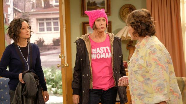 Roseanne stands with Jackie and Darlene in their living room.