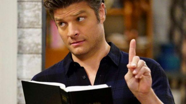 A man holding up a book and pointing a finger.