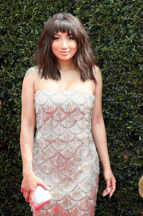 Jeannie Mai posing on a red carpet.