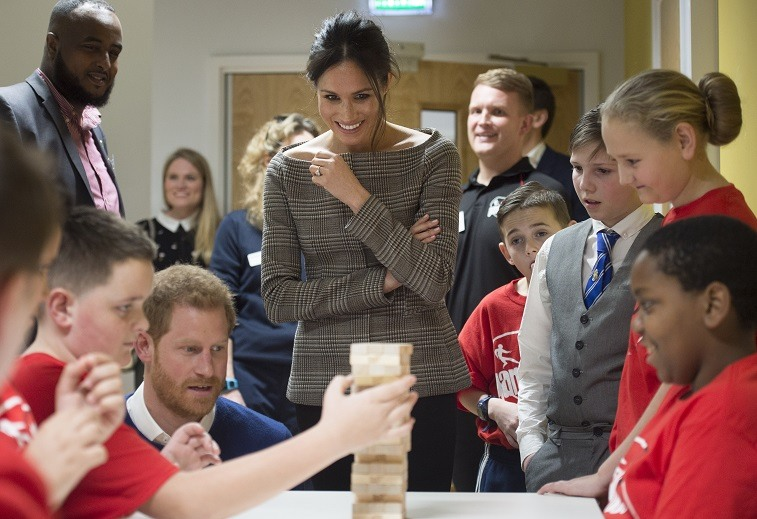 Prince Harry and his fiancee Meghan Markle watch a game of Jenga during their visit to Star Hub on January 18, 2018 in Cardiff, Wales.