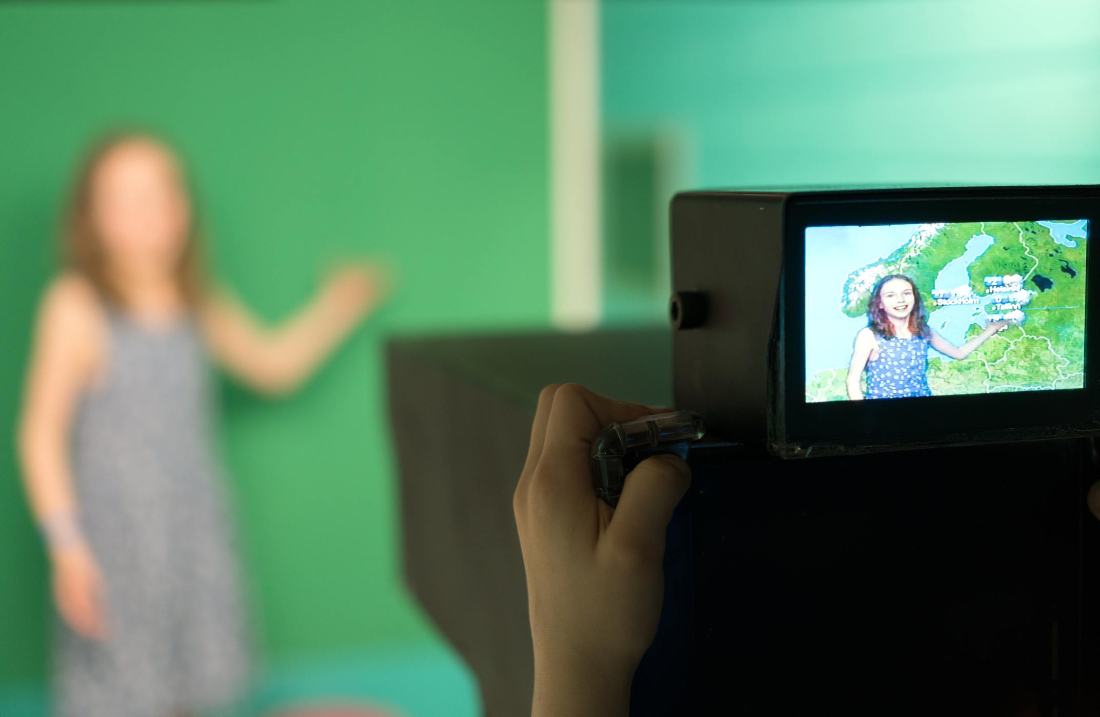Weather forecast. Little girl standing in front of camera on green screen.