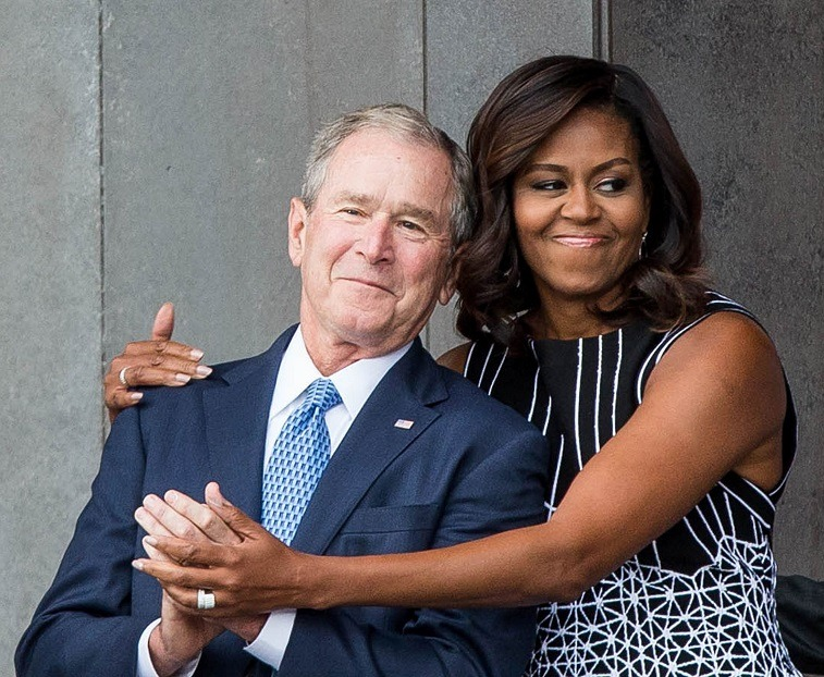 Former US President George W. Bush receives a hug from US First Lady Michelle Obama as they attend the opening ceremony for the Smithsonian National Museum of African American History and Culture on September 24, 2016 in Washington, D.C.