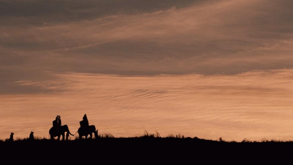 Two people on elephants seen in the horizon.