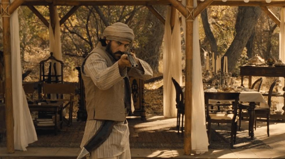 A host raising and aiming a shotgun.
